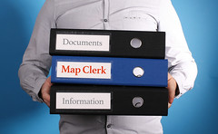 Map Clerk - Businessman is carrying a stack of 3 file folders on blue background