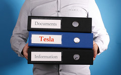 Tesla - Businessman is carrying a stack of 3 file folders on blue background