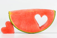 A slice of ripe watermelon with a carved heart