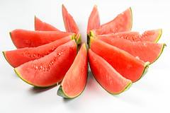 Cut pieces of fresh red watermelon on a white background