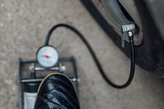 Aufpumpen eines Autoreifens mit einer Fußluftpumpe