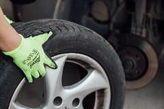 Person hält ein Autorad und im verschwommenen Hintergrund sichtbare Scheibenbremse und Autoachse. Radwechsel