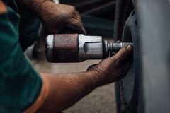 Reifentechniker schraubt Radmuttern mit einem Druckluft Schlagschrauber ab. Radwechsel