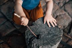 Kleinkind spielt mit einem kleinen Stock