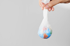 Woman holds the Earth in plastic bag. concepts of environmental and ecological problems, plastic pollution and climate change issues
