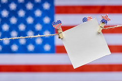 Blank card hanged on the rope with decorative clothespins colored in USA national symbols
