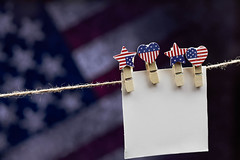 An empty paper card hanged with clothespin on the rope