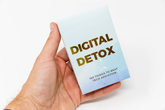 Digital detox: 100 things to beat tech addiction. Hand holds box of cards. Advice to disconnect, go offline
