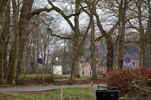 Havezate Mensinge door de bomen met 2 honden en een duiventil.