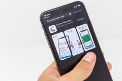 Smartphone mit der Corona-Warn-App in der Hand: die App hilft, Infektionsketten nachzuverfolgen