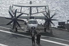 Sailors prepare an E-2C Hawkeye on the flight deck of the aircraft carrier USS Theodore Roosevelt (CVN 71).