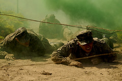 Special Warfare combatant-craft crewman candidates low-crawl under an obstacle.