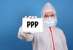 Medical doctor holding banner with PPP text, Isolated over blue background