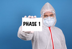 Medical doctor holding banner with Phase 1 text, Isolated over blue background