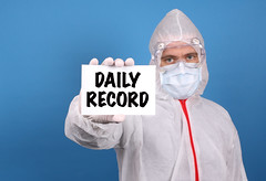 Medical doctor holding banner with Daily Record text, Isolated over blue background