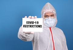 Medical doctor holding banner with Covid-19 Restrictions text, Isolated over blue background
