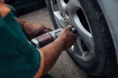 Tyre technician working with a compressed air impact wrench