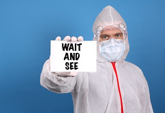 Medical doctor holding banner with Wait And See text, Isolated over blue background