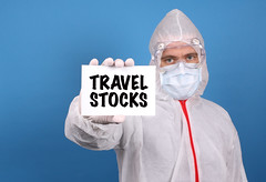 Medical doctor holding banner with Travel Stocks text, Isolated over blue background