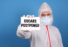 Medical doctor holding banner with Oscars Postponed text, Isolated over blue background