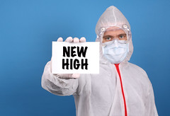 Medical doctor holding banner with New High text, Isolated over blue background