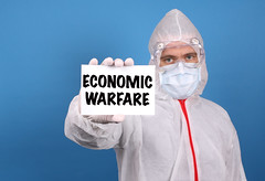 Medical doctor holding banner with Economic Warfare text, Isolated over blue background