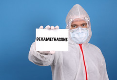 Medical doctor holding banner with Dexamethasone text, Isolated over blue background