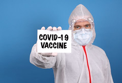 Medical doctor holding banner with Covid-19 Vaccine text, Isolated over blue background