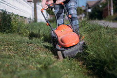 Young woman mowing a ditch in front of her property