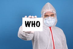 Medical doctor holding banner with WHO text, Isolated over blue background