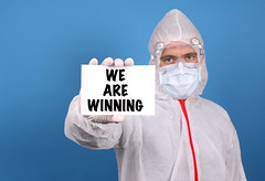 Medical doctor holding banner with We Are Winning text, Isolated over blue background