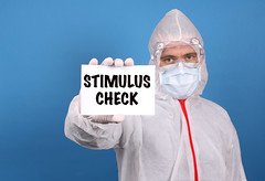 Medical doctor holding banner with Stimulus Check text, Isolated over blue background