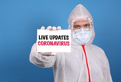Medical doctor holding banner with Live Updates Coronavirus text, Isolated over blue background