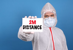 Medical doctor holding banner with 2M Distance text, Isolated over blue background