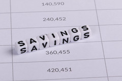 White cubes with Savings letters on financial document