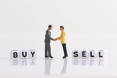 Two businessman shaking hands in front of Buy and Sell text