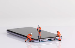 Miniature workers repairing smartphone on white table