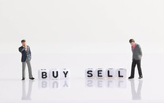 Two businessman with Buy and Sell text