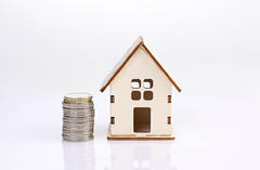 Small wooden house with coin stack on white background