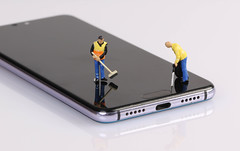 Miniature people workers cleaning smartphone screen