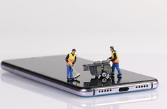 Miniature people workers cleaning smartphone screen on white background