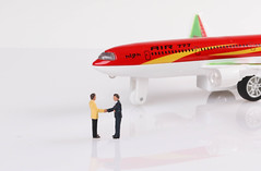 Businessman making agreement in front of airplane