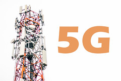 Cell tower and 5G text on a cloudy white sky