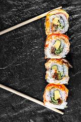 Sushi Rainbow Dragon on a black background with chopsticks