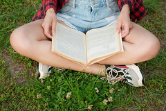 Reading a book in nature, a girl sits on the grass and reads a book