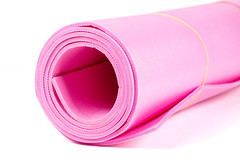 Pink yoga mat for exercise on white background