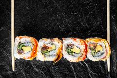 Wooden chopsticks and sushi Rainbow dragon on a black tray