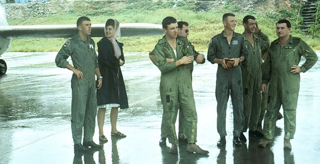 Photo:1967 Sheltering under the wing of RNZAF Bristol Freighter NZ5902 during a downpour at USAF Base Kadena, Okinawa are F/O Dave Geddes, F/L Hugh Francis, F/O Pete Hughan, F/O John Cotton and two USAF F-104 pilots; Thomas Mahan & Ace Rawlins, 18 Jul 1967. By Gary Danvers