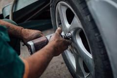Reifentechniker wechselt ein Auto-Rad
