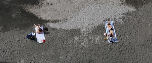Sunbathing on the black volcanic sand in Sorrento